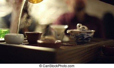 Tea ceremony in the cafe, the waiter pours the tea, the...