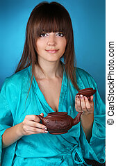 Tea ceremony with beautiful young woman on blue background