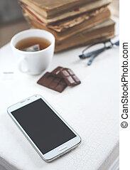Tea, chocolate, old books and smartphone