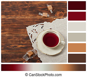 Tea Cup and Plate Of Fine Bone China. Sweets. Burnt Wooden Background. Natural Linen Napkin. Palette With Complimentary Colour Swatches