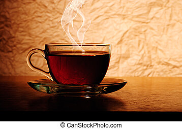 Tea cup - Glass cup of black tea on wooden table with smoke