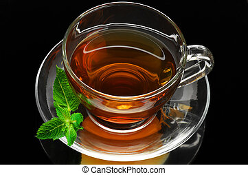 Glass cup of tea with mint on black background.