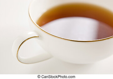 Tea cup on white background, close-up.
