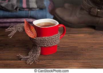 tea cup over a scarf, autumn leaf and set of seasonal clothes