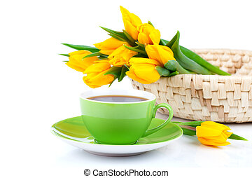 tea cup with bouquet of fresh yellow tulips on white background