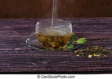 Tea flows in a transparent cup