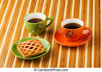 Tea in a bright cups and puff bun with jam in a saucer.