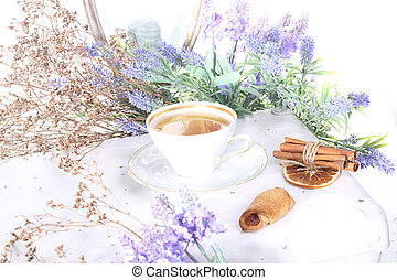 tea in a China Cup and a biscuit with jam