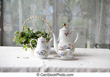 Tea in a cup, tea service on a table with a white cloth