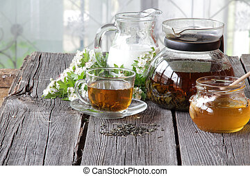 Tea in a transparent cup and a jug with milk