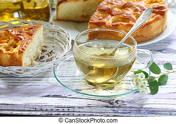 Tea in a transparent cup and a piece of a pie with a stuffing from apricots