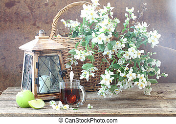 Tea in a transparent mug and a bouquet from jasmin branches in a wattled basket and an old lantern