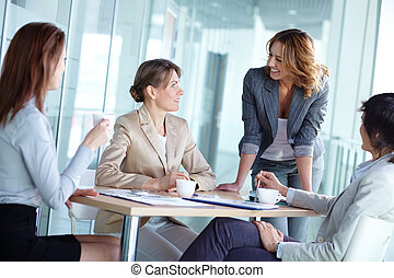 Tea in team - Image of four businesswomen interacting at...