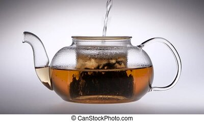 Tea is brewed in a glass teapot. Slow motion. Studio - Tea...