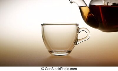 Tea is poured from teapot into glass cup. Slow motion