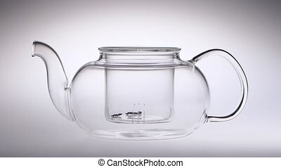 Tea leaves are falling in glass transparent teapot. Slow motion