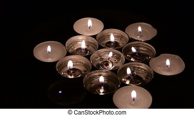Tea light candles rotating on a mirror background. Side view.