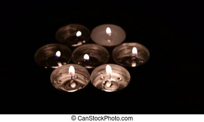 Tea light candles rotating on a mirror background. Top view of gold flame of candle. Closeup. Low DOF