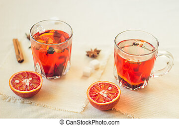 Tea made from dried fruit, seasoned with cinnamon cloves and anise seeds. There is an orange nearby