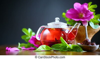 tea made from rose hips with mint on a wooden table with...