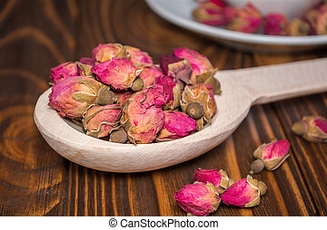 Tea of dry buds of roses in a wooden spoon