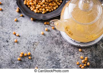 Tea of sea-buckthorn berries with branch on dark background.healthy drink