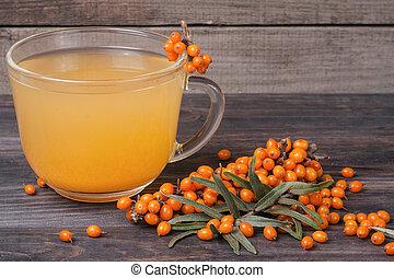 Tea of sea-buckthorn berries with branch on dark wooden background