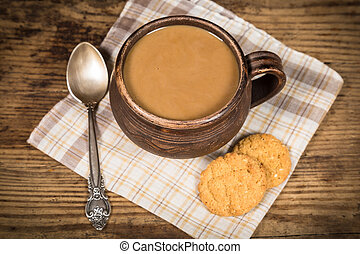 Tea or coffee cup with milk and cookies on wooden table