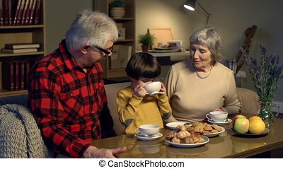 Tea Party - Caring grandparents treating grandson with...