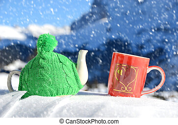 Tea pot in the knitted cap and red cup with a heart in the...