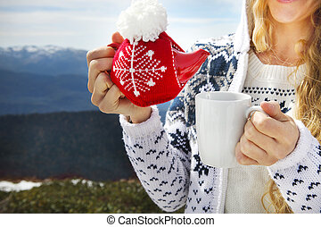 Tea pot in the knotted cap and cup in the hands of a woman against mountain scenery
