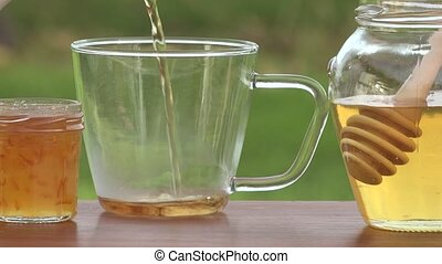 Tea poured into cup - on vineyards background