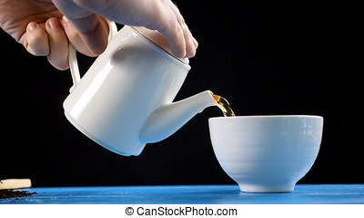 Tea pouring process from a kettle in a mug in slow motion on...