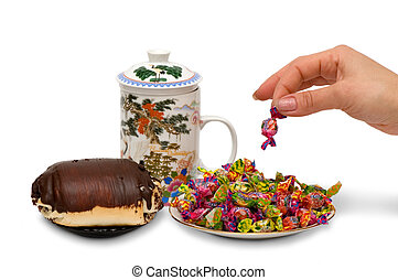 Tea, roll, sweets, a female hand.