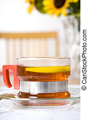 Tea series 4 - Glass cup of tea with lemon on a dining table...