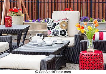Tea served on an outdoor patio between flowers
