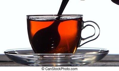 Tea spoon stir the drink in a glass cup. Closeup