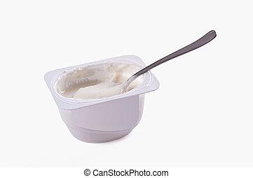 Tea spoon with yoghurt on a light background