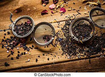 Tea stainers with aromatic tea on wooden table background