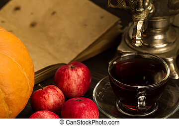 Tea still life with samovar, apples, ripe orange pumpkins, maple leaves on wooden background. Thanksgiving, autumn.