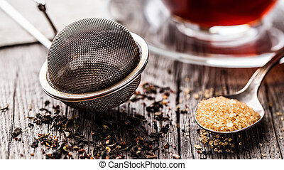 Tea strainer with tea leafs and brown sugar on rustic ...