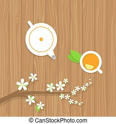 Tea teapot and a branch of the cherry blossoms on a wooden table.