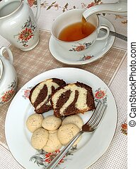 A table set for tea, with tea being poured and a plate of cake and cookies