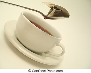 Off-white themed tea series - Spoon with teabag dripping water into a hot cup of tea.