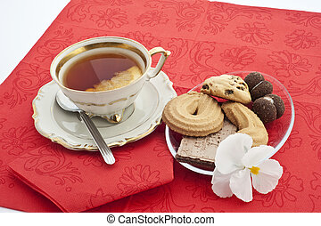 cup of tea with lemon and plate of biscuits