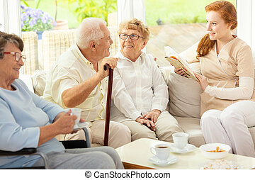 Tea time for seniors sitting on a couch in a common room of a luxury retirement home. Caretaker reading a book to elderly.