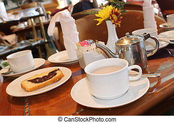 Restaurant table with tea cups and a slice of cake decorated with orange flowers and waiter's pushing food cart in the background