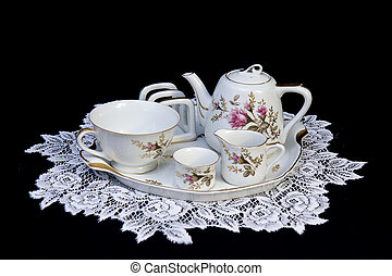 Tea set on lace doily with pink flowers on black background