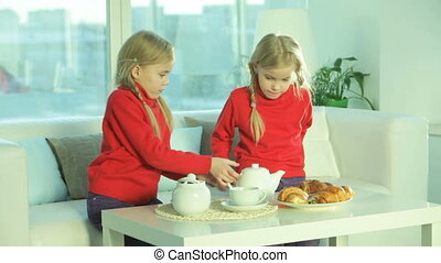 Tea time - Twin girls having tea with croissants at home