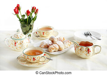 Two cups of tea with small sweet rolls